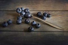 Czarne jagody w nieociosanym kuchennym położeniu z starym drewnianym tłem Zdjęcia Stock