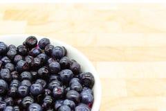 Czarne jagody w zaokrąglonym pucharze na drewnianym stole fotografia stock