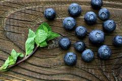 Czarne jagody z niektóre nowymi liśćmi na antykwarskim drewnianym stole Zdjęcia Royalty Free