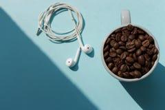 Czarne kawowe fasole w błękitnej filiżance i białych hełmofonach na błękitnym tle z światłem słonecznym ocieniają odgórnego widok obrazy stock