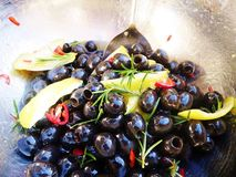 Czarne oliwki z cytryną, chili i rozmarynami, obraz stock