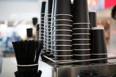 Czarne papierowe filiżanki na kontuarze przeciw tłu zamazany kawowy bar przy centrum handlowym z takeaway kawą iść Zdjęcie Stock