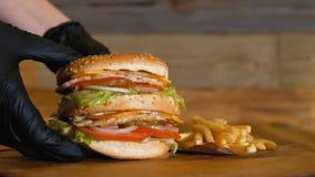 Czarne rękawiczki stawiają soczystego hamburger z dwa warzywami na drewnianej desce i cutlets obok francuskich dłoniaków niezdrow zbiory wideo