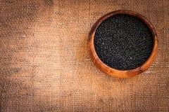 Czarne soczewicy w drewnianym pucharze Fotografia Royalty Free