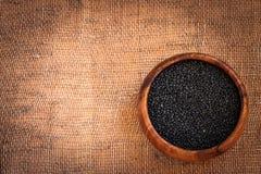 Czarne soczewicy w drewnianym pucharze Zdjęcie Stock