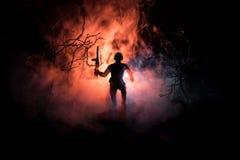 Czarne sylwetki żołnierz w dymią pożarniczego płonącego chodzenie w batalistycznej operaci back light stonowany Zdjęcie Stock