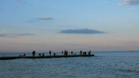 czarne upadku wiecz?r fala morza Ludzie chodzą wzdłuż falochronu na i podziwiają zmierzch ciepłym, spokojnym lato wieczór, zdjęcie wideo