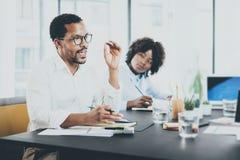 Czarnego Afrykanina kierownik projektu explaning biznesowego zadanie w pokoju konferencyjnym Dwa młodego przedsiębiorcy pracuje w Obrazy Royalty Free
