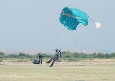 Czarnego Afrykanina męski skydiver robi bezpiecznemu lądowaniu na trawie z op Obrazy Stock