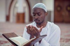 Czarnego Afrykanina Muzułmański mężczyzna ono Modli się W meczecie z otwartą świętą księgą Koran Obrazy Stock