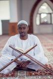 Czarnego Afrykanina Muzułmański mężczyzna ono Modli się W meczecie z otwartą świętą księgą Koran Zdjęcie Royalty Free