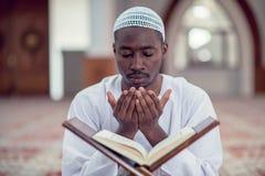 Czarnego Afrykanina Muzułmański mężczyzna ono Modli się W meczecie z otwartą świętą księgą Koran Zdjęcia Stock