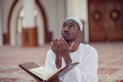 Czarnego Afrykanina Muzułmański mężczyzna ono Modli się W meczecie z otwartą świętą księgą Koran Obraz Royalty Free