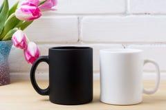 Czarnego kawowego kubka i bielu cappuccino filiżanki mockup z różowym tulipanem Fotografia Royalty Free