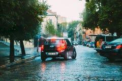 Czarnego koloru Mini Cooper Samochodowy krajan Iść W deszczu Na ulicie Obraz Stock