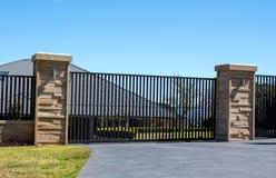 Czarnego metalu podjazdu wejściowe bramy ustawiać w piaskowcowej cegle one fechtują się z mieszkaniowym ogródem obraz stock