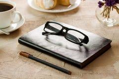 Czarnego rzemiennego notepad widowisk czarnooprawny pióro Fotografia Stock