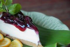 Czarnej jagody cheesecake dekorujący na zielonym bananowym liściu Zdjęcie Stock