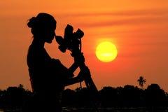 Czarnej sylwetki kobiety trwanie przytulenie lotosowego kwiatu zmierzch zdjęcia royalty free