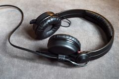 Czarni audio modnisiów hełmofony z sznura lying on the beach na popielatym tle fotografia stock
