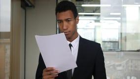 Czarni biznesmena czytania dokumenty w biurze zdjęcia royalty free