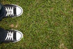 Czarni brezentowi sneakers na trawie zdjęcia royalty free