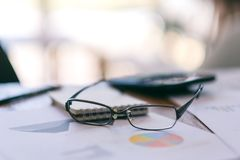 Czarni eyeglasses z papierkową robotą na stole obrazy royalty free