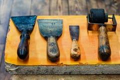 Czarni gumowi rolownika, dużych i małych kit noże, pomarańcze kamienia talerza tło Artysty decorator akcesoria handyman Obrazy Royalty Free