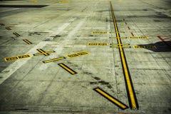 Czarni i żółci lotniskowi ocechowania na betonie Fotografia Stock