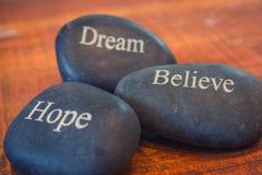 Czarni inspiracyjni otoczaków kamienie z słowami Marzą, Wierzą, Fotografia Stock