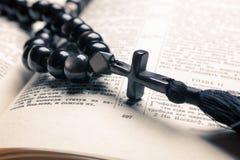 Czarni kamienni chrześcijaństwo koraliki z krzyżem na biblii obraz stock