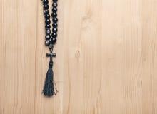 Czarni kamienni chrześcijaństwo koraliki z krzyżem na drewnianym biurku zdjęcie stock