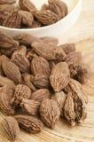 Czarni kardamonów strąki na drewnianym tle Fotografia Stock