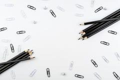 Czarni ołówki i papierowe klamerki, biel zapinają i papierowe klamerki kłamają na białym tle obraz stock