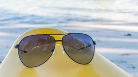 Czarni okulary przeciwsłoneczni na żółtym kajaku bielu plażowym tle i Zdjęcia Royalty Free