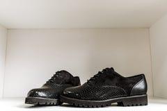 Czarni patentowi rzemienni buty z sk?ra wzorem przeciw bia?ej p??ce w sklepie zdjęcie stock