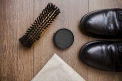 Czarni rzemienni buty na drewnianej podłoga Zdjęcia Royalty Free
