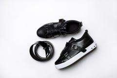 Czarni rzemienni sneakers z patkami, biel podeszwa i rzemienny czarny pasek na bia?ym tle zdjęcie royalty free