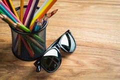 Czarni słońc szkła z wiązką kolorów ołówki w stojaku Fotografia Stock