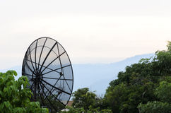 Czarni satelitarni dishs na tle zielony drzewo i niebo Zdjęcia Royalty Free