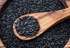 Czarni sezamowi ziarna w drewnianej łyżce Sezamowi ziarna w naczyniu przy tłem Odgórny widok zdjęcie stock