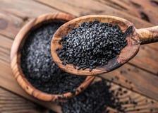 Czarni sezamowi ziarna w drewnianej łyżce Stary drewniany stół i naczynie przy tłem Odgórny widok zdjęcie royalty free