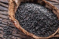 Czarni sezamowi ziarna w organicznie pucharze na starym drewnianym stole Odgórny widok obrazy royalty free