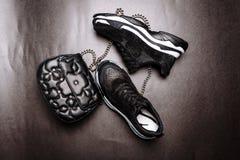 Czarni sneakers na bia?ej g?stej podeszwie dekoruj?cej z czerni? b?yskaj? i czarny sprz?g?o z asteryskami na ?a?cuchu na szaro?ci fotografia stock