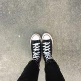Czarni sneakers na dziewczyn nogach Kobieta w czarnych cajgach i sneakers cieszy się dzień w mieście Obrazy Stock