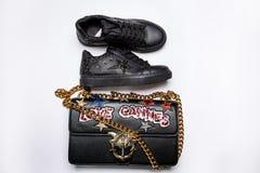 Czarni sneakers ozdabiaj?cy z gwiazd? czer? b?yskaj? i czarna torba z z?oto ?a?cuchem ozdabiaj?cym z b?yszcz?cymi gwiazdami, ceki zdjęcia royalty free