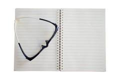Czarni szkła umieszczający na notatniku, odizolowywającym na białym tle Zdjęcie Royalty Free