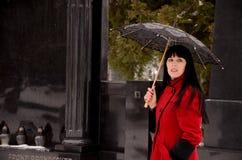 Czarni włosy kobiety na cmentarzu z parasolem Obraz Stock