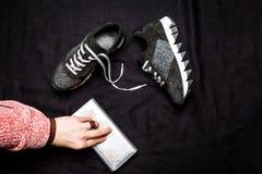 Czarni zamszowy sneakers dekorowali z srebnymi cekinami i żeńską ręką z srebną kiesą na czarnym wyplatającym tle zdjęcie royalty free