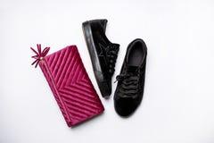 Czarni zamszowy sneakers i aksamitny purpury sprzęgło nad białym tłem fotografia stock